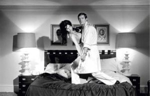 Roger Moore and Madeline Smith (on bed)